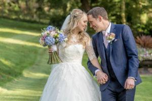 happy bride and groom at Wentbridge House Hotel in the gardens walking