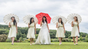 Bride and bridesmaids with brollys