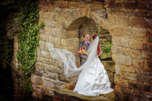 Flowing veil shot with the bride and groom under the arch at Waterton Park in Wakefield