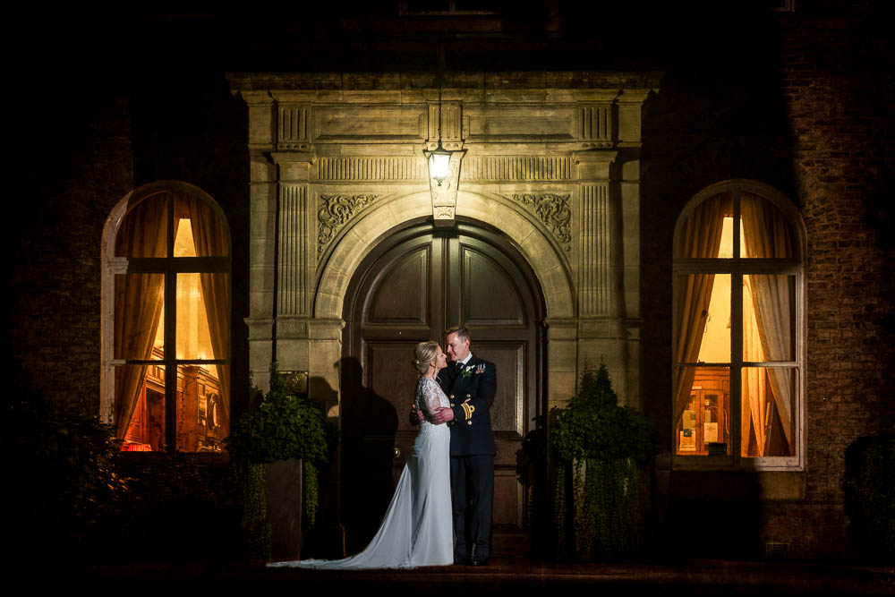 Night time shot of bride and groom outside main door of The Hawkhills near York