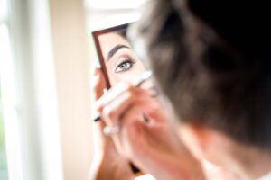 Bride looking in the mirror putting on her make up at Wentbridge House Hotel