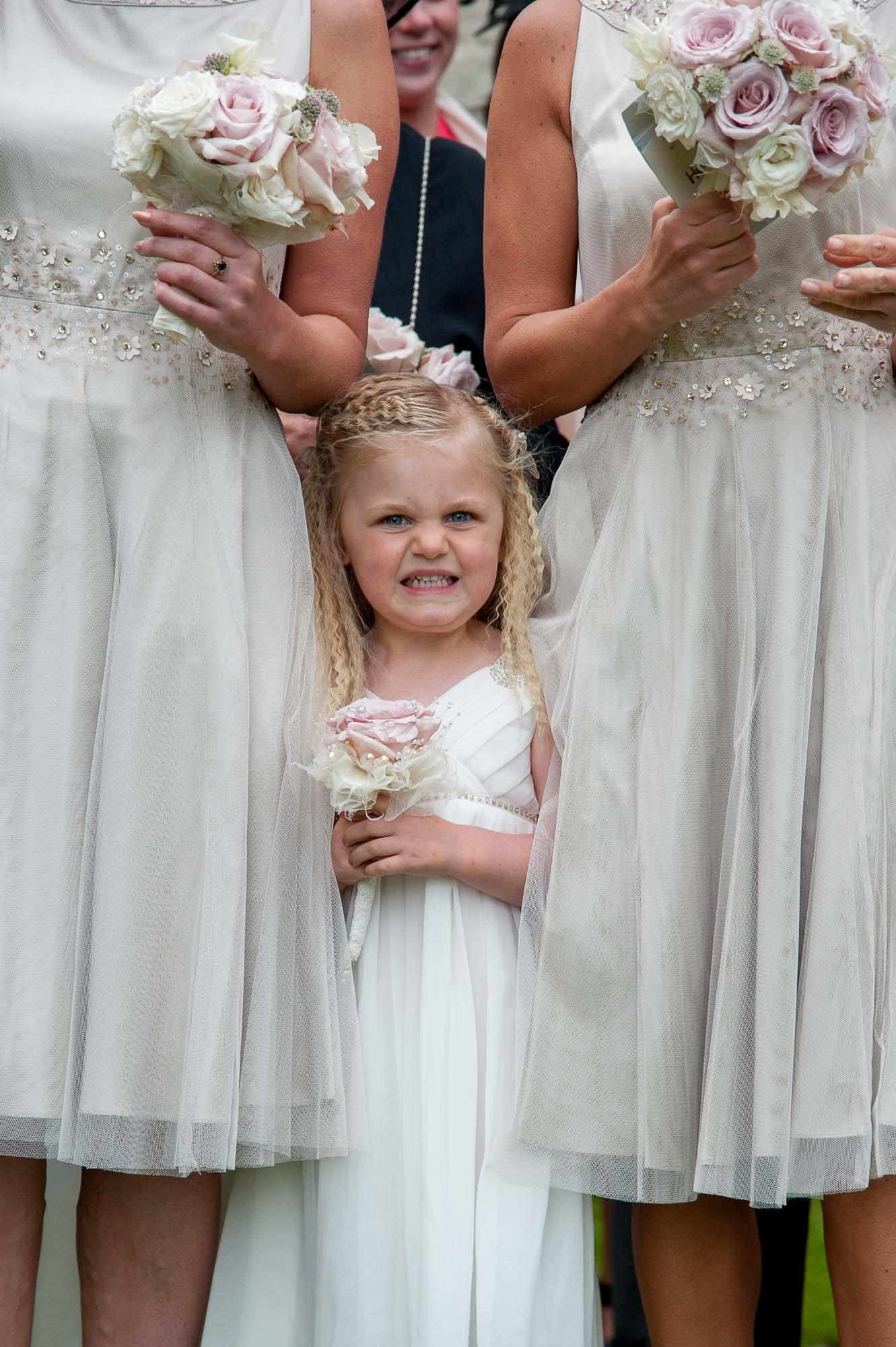 Flower girl peeping from between bridesmaids