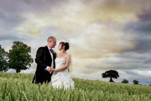 Bride and Groom in wheat field at Rogerthorpe Manor Hotel In Pontefract