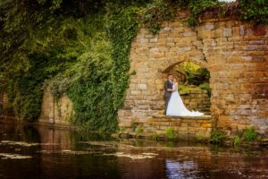 Bride and groom under the arch at Waterton Park Hotel near Wakefield