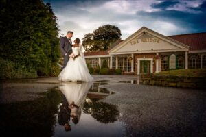 Bride and groom in water reflection at The Bridge Inn in Wetherby