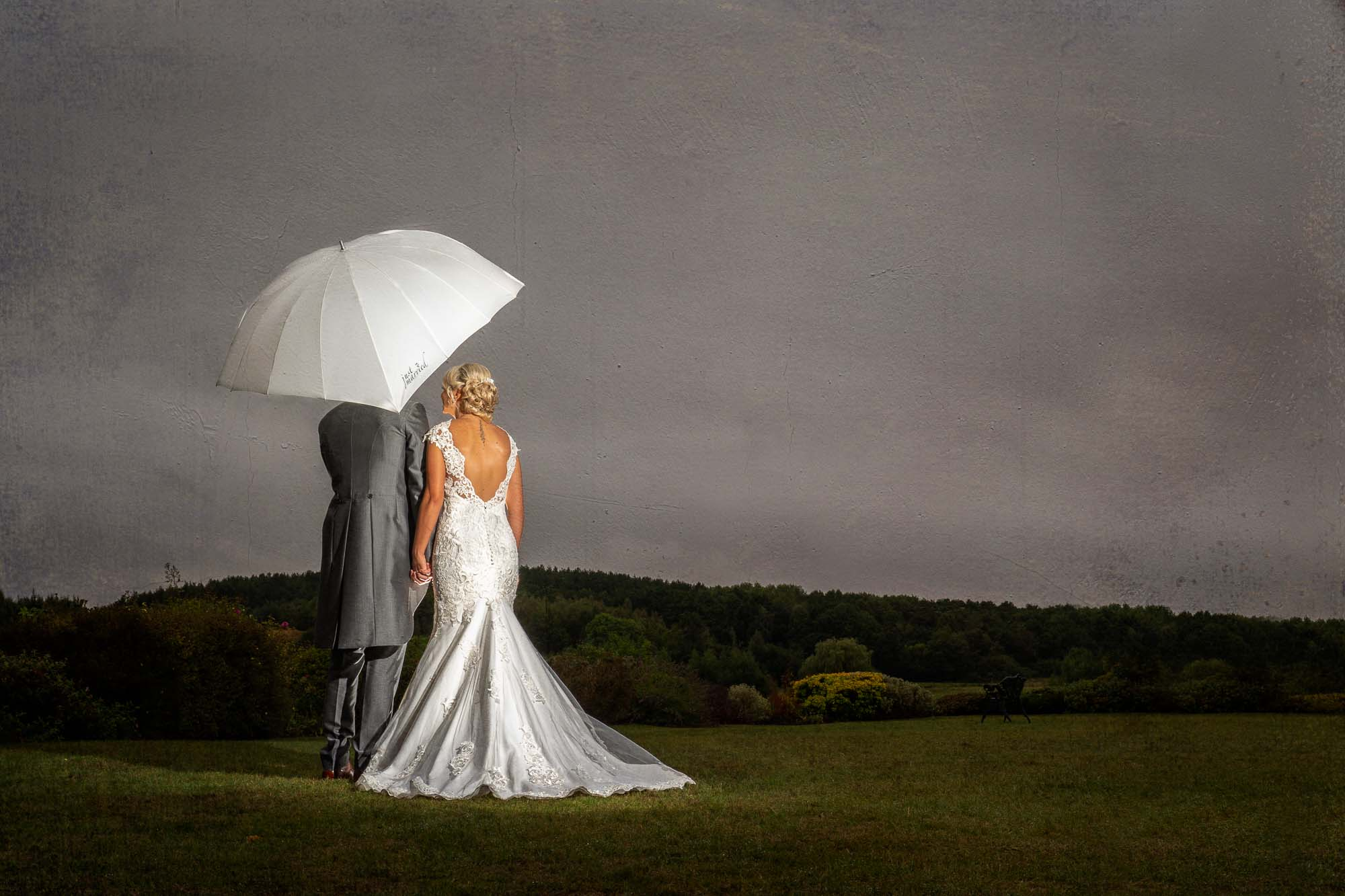 Bride and groom in the rain with umbrella at Waterton Park in Wakefield