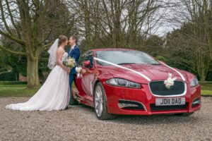 Bride and groom photographed next to car at Saltmarshe Hall near Goole and Selby
