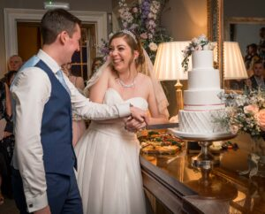 Bride and groom cutting wedding cake at Saltmarshe Hall in Selby