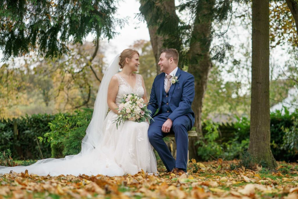 Bride and groom sitting down on a bench photographed at Wentbridge House Hotel