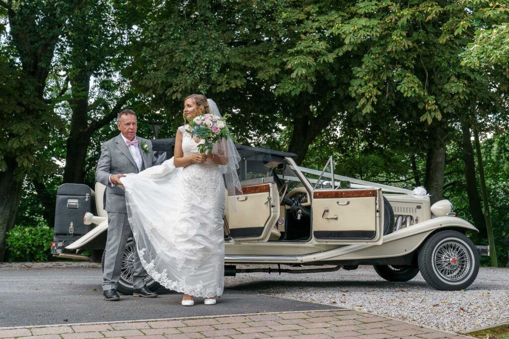 Bride getting out of car at Woodlands Hotel in Leeds