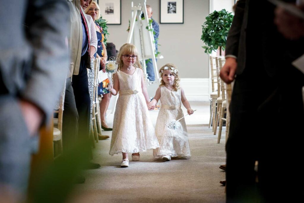 Flower girls walk down the aisle at Woodlands Hotel in Leeds