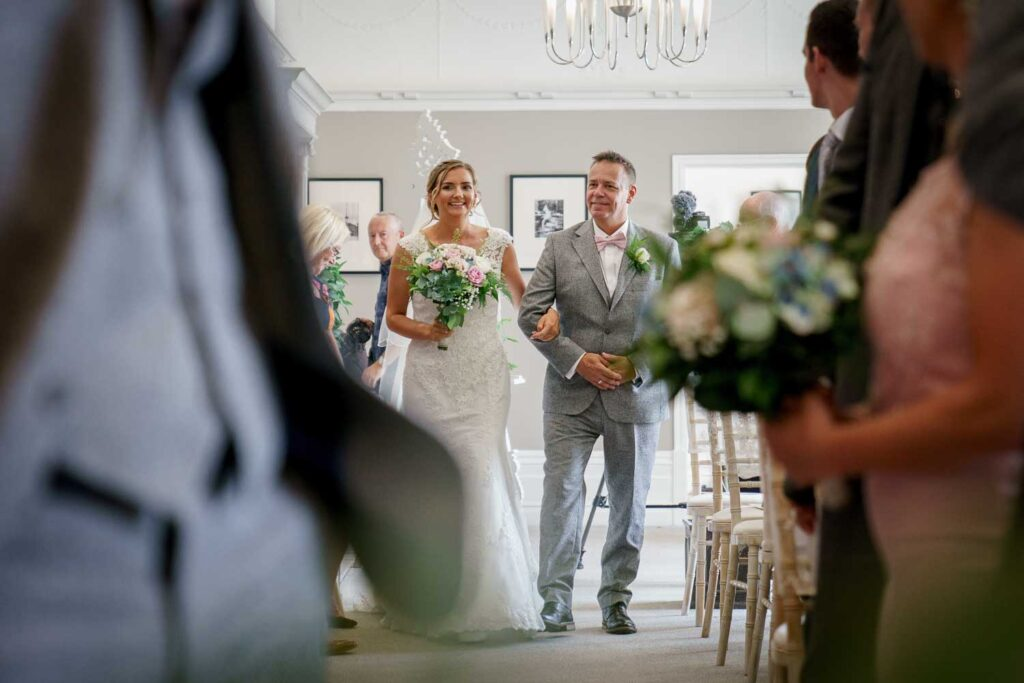 Bride walking down the aisle at Woodlands Hotel in Leeds