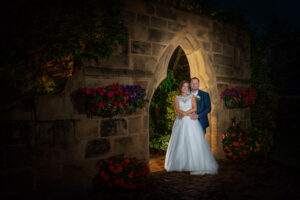 Night time photograph of bride and groom at Rogethorpe Manor Hotel