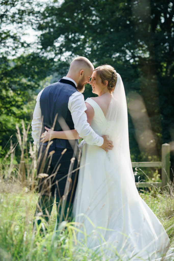Bride and groom at wedding in long grass at Wentbridge House Hotel